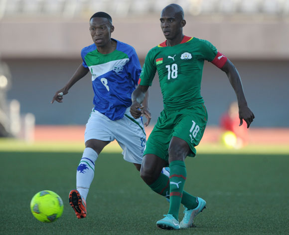 Charles Kabore of Burkina Faso challenged by Mohau Ramonneng of Lesotho during the 2015 African Cup of Nations Qualifiers match between Lesotho and Burkina Faso at Setsoto Stadium, Maseru on the 15 November 2014