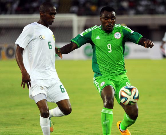 Anele Ngcongca of South Africa challenges Emmanuel Emenike of Nigeria on Wednesday
