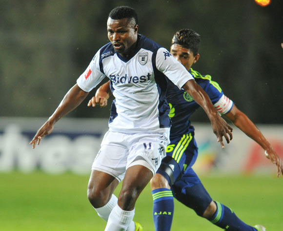 Chris Katongo of Bidvest Wits challenged by Travis Graham of Ajax Cape Town during the Absa Premiership 2014/15 football match between Bidvest Wits and Ajax Cape Town at the Bidvest Stadium in Johannesburg, South Africa on December 10, 2014
