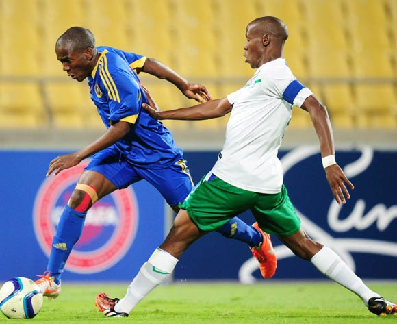 Mthunzi Mkhontfo of Swaziland tackled by Nkau Lerotholi of Lesotho during the 2015 Cosafa Cup match between Lesotho and Swaziland at the Royal Bafokeng Stadium, Rustenburg on the 20 May 2015