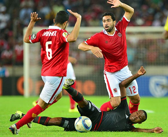 Thamsanqa Gabuza of Orlando Pirates fouled by Sabry Abdelmontelb (l) and Ahmed Fathi of Al Ahly (r) during the 2015 CAF Confederation Cup semifinal, first leg football match between Orlando Pirates and Al Ahly of Egypt at Orlando Stadium in Johannesburg, South Africa on 26 September, 2015 ©Gavin Barker/BackpagePix