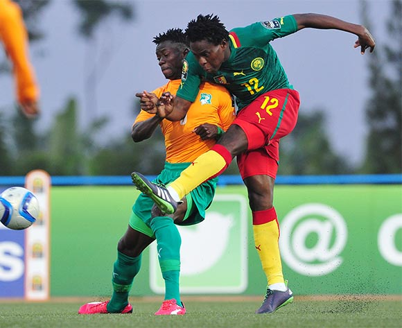 Samuel Nlend of Cameroon shoots at goal as he is challenged by Soualio Dabila Ouattara of Ivory Coast during the 2016 CHAN Rwanda quarterfinal between Cameroon and Ivory Coast at Huye Stadium, Butare on 30 January 2016 ©Ryan Wilkisky/BackpagePix
