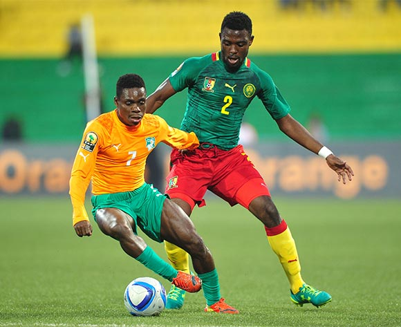 Djobo Atcho of Ivory Coast controls the ball as he is challenged by Joseph Ngwem of Cameroon