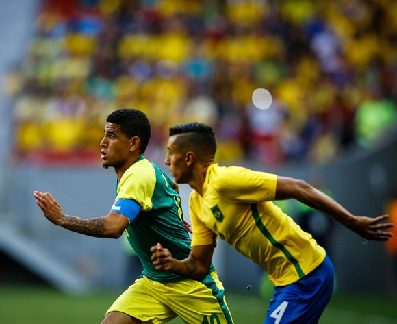 epa05455427 Keagan Dolly (L) of South Africa in action against Marquinhos (R) of Brazil during the men's first round match between Brazil and South Africa for the Rio 2016 Olympic Games Soccer tournament at Mane Garrincha stadium in Brasilia, Brazil, 04 August 2016.  EPA/FERNANDO BIZERRA JR.