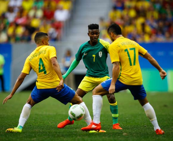 epa05455510 Menzi Masuku (C) of South Africa in action against Marquinhos (L) and Felipe Anderson (R) of Brazil  during the men's preliminary round match between Brazil and South Africa for the Rio 2016 Olympic Games Soccer tournament at Mane Garrincha stadium in Brasilia, Brazil, 04 August 2016.  EPA/FERNANDO BIZERRA JR.