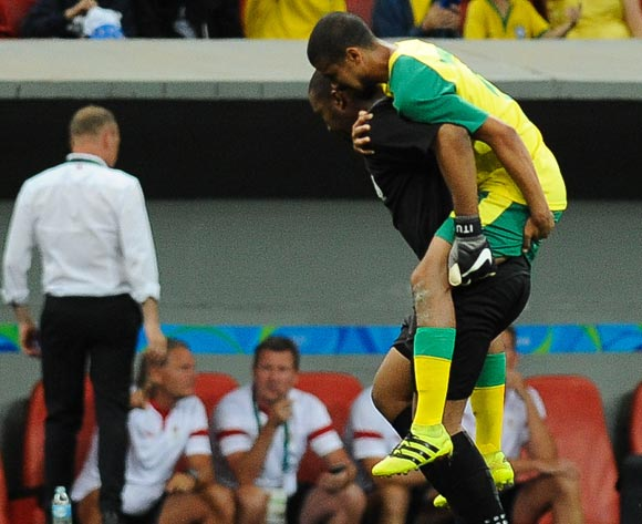 epa05463700 Goalkeeper Itumeleng Khune (L) of South Africa carries his teammate Abbubaker Mobara during the men's preliminary round group A match between Denmark and South Africa of the Rio 2016 Olympic Games Soccer tournament at the Mane Garrincha Stadium in Brasilia, Brazil, 07 August 2016.  EPA/ANDRESSA ANHOLETE BRAZIL OUT