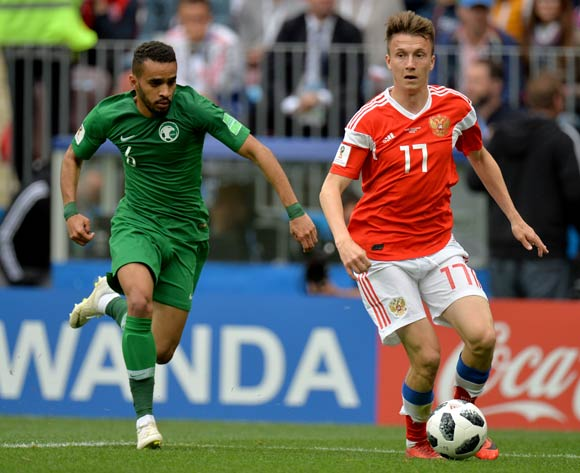 epa06807391 Mohammed Alburayk (L) of Saudi Arabia in action against Aleksandr Golovin of Russia during the FIFA World Cup 2018 group A preliminary round soccer match between Russia and Saudi Arabia in Moscow, Russia, 14 June 2018.