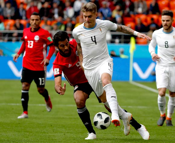 epa06809672 Guillermo Varela of Uruguay (CR) and Marwan Mohsen of Egypt (CL) during the FIFA World Cup 2018 group A preliminary round soccer match between Egypt and Uruguay in Ekaterinburg, Russia, 15 June 2018.