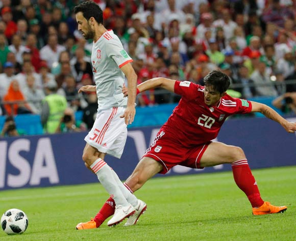 epa06825488 Sergio Busquets (L) of Spain and Sardar Azmoun of Iran in action during the FIFA World Cup 2018 group B preliminary round soccer match between Iran and Spain in Kazan, Russia, 20 June 2018.