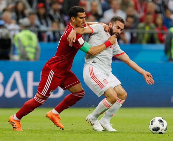 epa06825508 Ehsan Haji Safi (L) of Iran and Dani Carvajal of Spain in action during the FIFA World Cup 2018 group B preliminary round soccer match between Iran and Spain in Kazan, Russia, 20 June 2018.