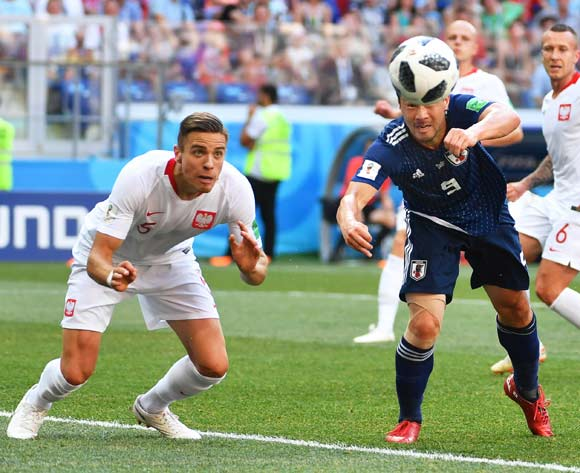 epa06847472 Poland's Jan Bednarek (L) in action against Japan's Shinji Okazaki (R)  during the FIFA World Cup 2018 group H preliminary round soccer match between Japan and Poland in Volgograd, Russia, 28 June 2018.