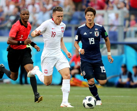 epa06847498 Hiroki Sakai of Japan (R) and Piotr Zielinski of Poland (C) in action during the FIFA World Cup 2018 group H preliminary round soccer match between Japan and Poland in Volgograd, Russia, 28 June 2018.