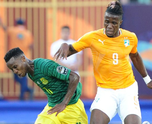 Themba Zwane of South Africa is fouled by Wilfried Zaha of Ivory Coast during the 2019 Africa Cup of Nations Finals game between Ivory Coast and South Africa at Al Salam Stadium in Cairo, Egypt on 24 June 2019 © Ryan Wilkisky/BackpagePix