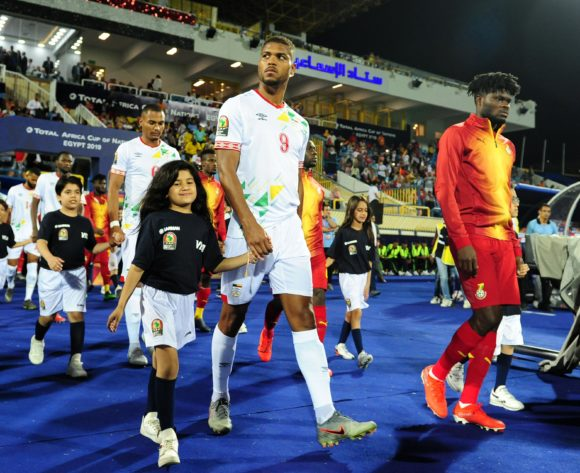 Steve Mounie of Benin walks to pitch with mascot during the 2019 Africa Cup of Nations Finals game between Ghana and Benin at Ismailia Stadium in Ismailia, Egypt on 25 June 2019 © Ryan Wilkisky/BackpagePix