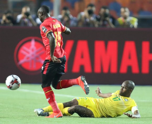 Godfrey Walusimbi of Uganda tackled by Knowledge Musona of Zimbabwe during the 2019 Africa Cup of Nations Finals match between Uganda and Zimbabwe at Cairo International Stadium, Cairo, Egypt on 26 June 2019 ©Samuel Shivambu/BackpagePix