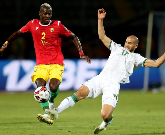 Mohamed Yattara of Guinea challenged by Adlane Guedioura of Algeria during the 2019 Africa Cup of Nations Finals last 16 match between Algeria and Guinea at 30 June Stadium, Cairo, Egypt on 07 July 2019 ©Samuel Shivambu/BackpagePix
