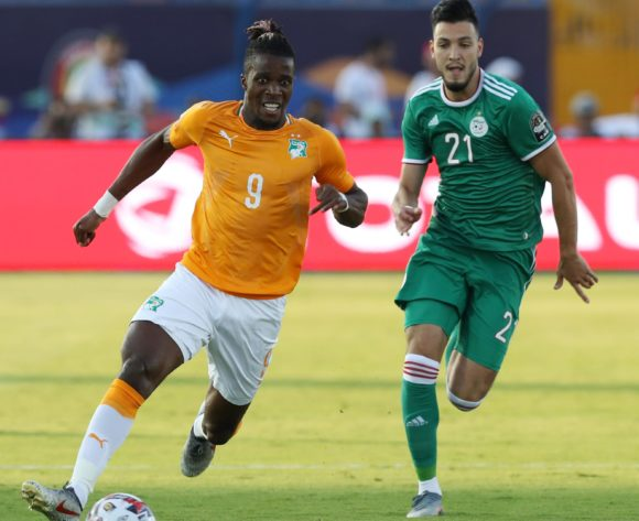 Wilfried Zaha of Ivory Coast challenged by Amir Bensebaini of Algeria during the 2019 Africa Cup of Nations Finals, quarterfinals match between Ivory Coast and Algeria at Suez Stadium, Suez, Egypt on 11 July 2019 ©Samuel Shivambu/BackpagePix