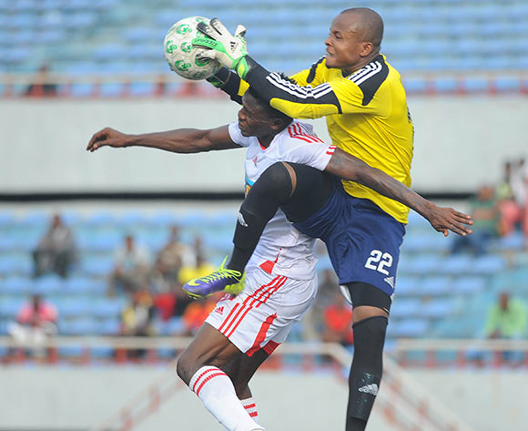 Ikechukwu Ezenwa of Sunshine Stars is challenged by Razaq Adegbite of Rangers during the Glo Nigeria Premier League 2014  match between Rangers and Sunshine Stars on April 6, 2014 at Nnamdi Azikiwe Stadium, Enugu, Enugu state